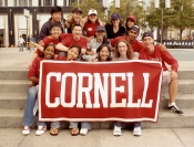 Cornell students holding a red Cornell banner